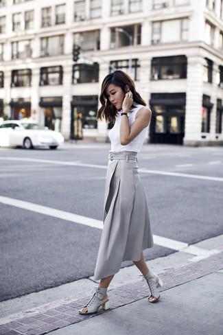Cómo combinar: sandalias de tacón de cuero grises, falda midi plisada gris, jersey de cuello alto sin mangas blanco