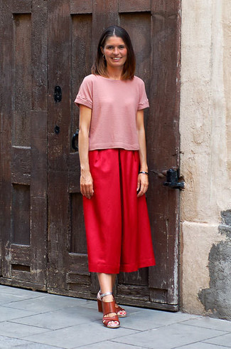 Cómo combinar: sandalias de tacón de cuero marrónes, falda pantalón roja, camiseta con cuello circular rosada