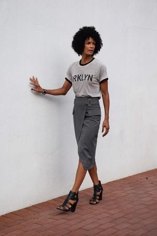 Cómo combinar: sandalias de tacón de cuero negras, falda midi gris, camiseta con cuello circular estampada gris