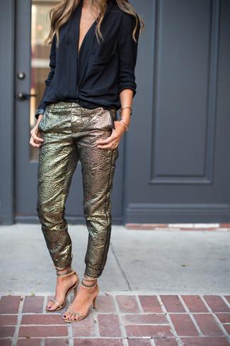 Cómo combinar: sandalias de tacón de cuero plateadas, pantalones pitillo dorados, blusa de manga larga negra