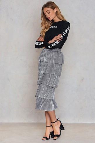 Cómo combinar: sandalias de tacón de terciopelo negras, falda midi plisada plateada, camiseta de manga larga estampada en negro y blanco