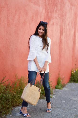Cómo combinar: bolsa tote de paja marrón claro, sandalias de tacón de lona de cuadro vichy en azul marino y blanco, vaqueros azul marino, túnica blanca