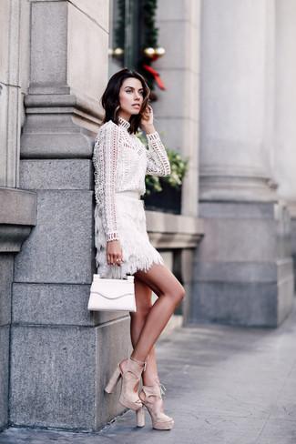 Cómo combinar: cartera sobre de cuero blanca, sandalias de tacón de ante en beige, minifalda сon flecos blanca, blusa de manga larga con ojete blanca