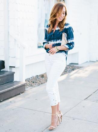 Cómo combinar: cartera sobre de paja en beige, sandalias de tacón de cuero en beige, pantalón capri blanco, camisa de vestir efecto teñido anudado en azul marino y blanco
