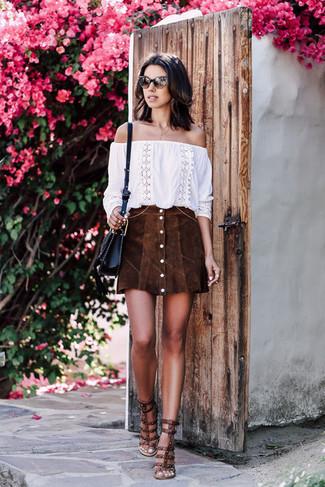 Cómo combinar: bolso bandolera de cuero negro, sandalias de tacón de cuero con tachuelas en marrón oscuro, falda con botones de ante en marrón oscuro, top con hombros descubiertos bordado blanco