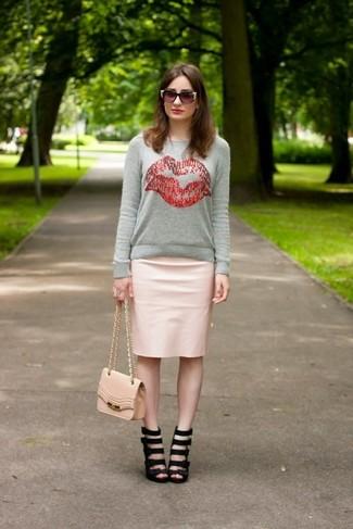 Cómo combinar: bolso bandolera de cuero rosado, sandalias de tacón de cuero negras, falda lápiz de cuero rosada, jersey con cuello circular estampado gris