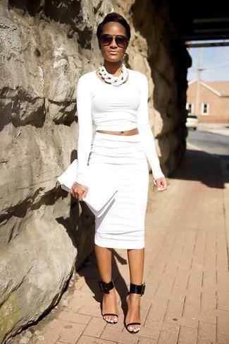 Cómo combinar: cartera sobre de cuero blanca, sandalias de tacón de cuero negras, falda lápiz blanca, jersey corto blanco