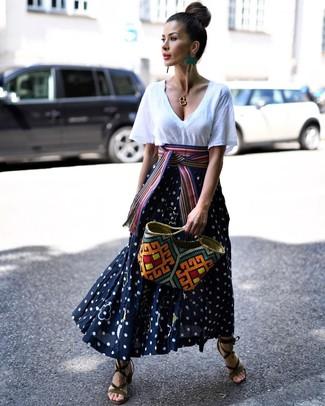 Cómo combinar: bolsa tote de paja en multicolor, sandalias de tacón de ante verde oliva, falda larga a lunares en azul marino y blanco, camiseta con cuello en v blanca