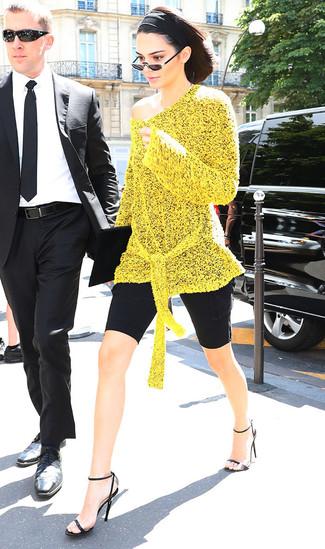 Cómo combinar: cartera sobre de ante negra, sandalias de tacón de cuero negras, mallas ciclistas negras, túnica de punto amarilla