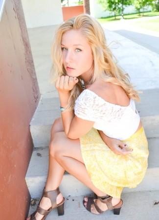 Cómo combinar: pulsera celeste, sandalias de tacón de cuero marrónes, falda skater con print de flores amarilla, top corto de encaje blanco