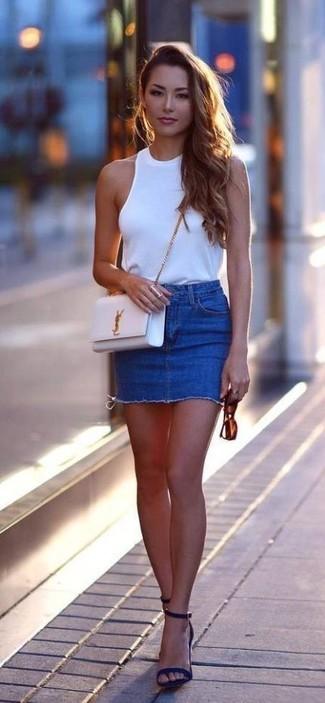 Cómo combinar: bolso bandolera de cuero blanco, sandalias de tacón de ante azul marino, minifalda vaquera azul, blusa sin mangas blanca
