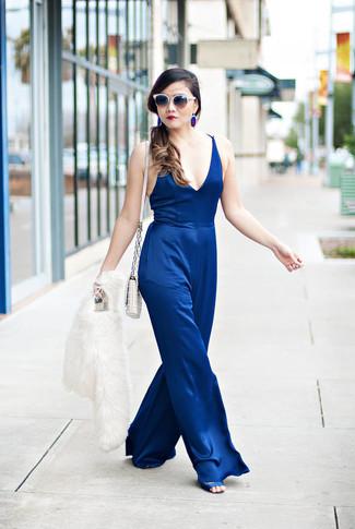 Cómo combinar: bolso bandolera de cuero acolchado blanco, sandalias de tacón de satén azules, mono azul, chaqueta de piel blanca