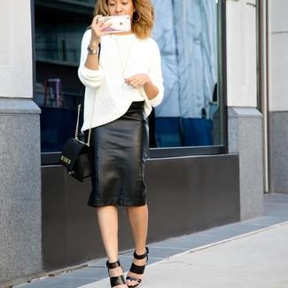 Cómo combinar: bolso bandolera de cuero negro, sandalias de tacón de cuero negras, falda lápiz de cuero negra, jersey oversized de punto blanco