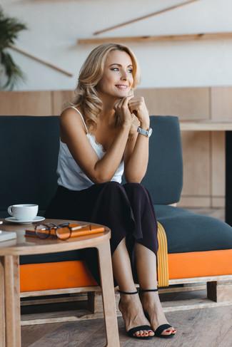 Cómo combinar: reloj de cuero gris, sandalias de tacón de ante negras, falda midi negra, camiseta sin manga de encaje blanca