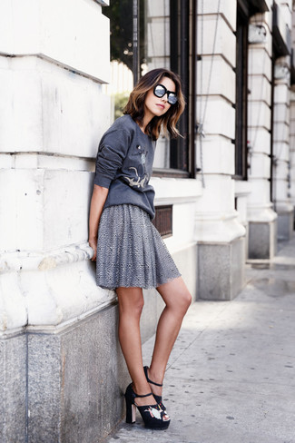 Combinar unas sandalias de tacón de ante bordadas negras: Una sudadera estampada en gris oscuro y una falda skater gris son una opción muy buena para el fin de semana. Sandalias de tacón de ante bordadas negras son una opción muy buena para complementar tu atuendo.