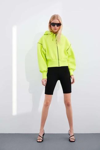 Cómo combinar: gafas de sol negras, sandalias de tacón de cuero negras, mallas ciclistas negras, sudadera con capucha en amarillo verdoso