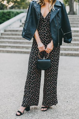 Cómo combinar: cartera sobre de cuero negra, sandalias de tacón de ante negras, mono con print de flores negro, chaqueta motera de cuero negra