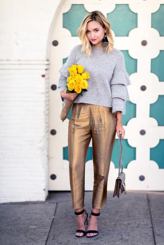 Cómo combinar: bolso de hombre de lona en beige, sandalias de tacón de ante negras, pantalón de pinzas dorado, jersey con cuello circular gris