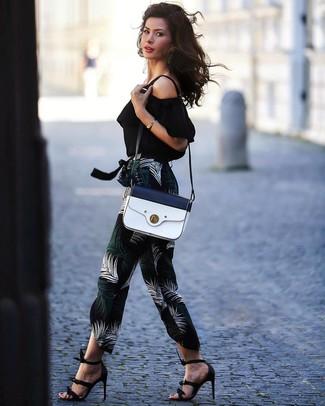 Cómo combinar: bolso bandolera de cuero en blanco y azul marino, sandalias de tacón de cuero negras, pantalón de pinzas estampado negro, top con hombros descubiertos negro