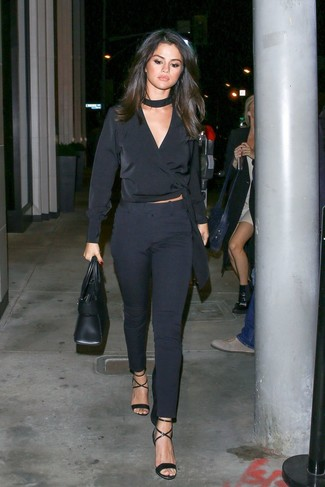 Cómo combinar: bolsa tote de cuero negra, sandalias de tacón de cuero negras, pantalones pitillo azul marino, blusa de manga larga de seda negra