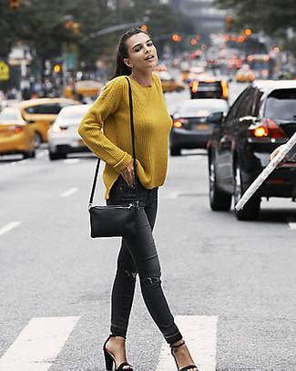 Cómo combinar: bolso bandolera de cuero negro, sandalias de tacón de ante negras, vaqueros pitillo desgastados negros, jersey oversized mostaza