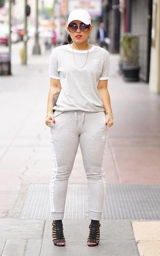 Cómo combinar: gorra inglesa blanca, sandalias de tacón de cuero negras, pantalón de chándal gris, sudadera gris