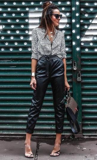 Cómo combinar: bolso de hombre de cuero estampado marrón, sandalias de tacón de goma transparentes, pantalón de pinzas de cuero negro, blusa de botones de leopardo en blanco y negro