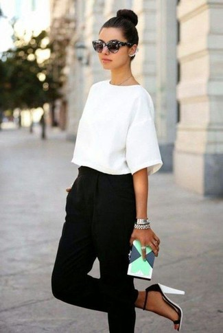 Cómo combinar: cartera sobre de cuero con estampado geométrico en verde menta, sandalias de tacón de cuero en blanco y negro, pantalón de pinzas negro, blusa de manga corta blanca