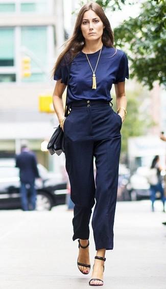 Cómo combinar: bolso bandolera de cuero negro, sandalias de tacón de cuero negras, pantalones anchos azul marino, camiseta con cuello circular azul marino