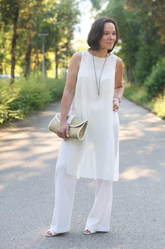 Cómo combinar: cartera sobre de paja marrón claro, sandalias de tacón de cuero blancas, pantalones anchos blancos, túnica de seda blanca