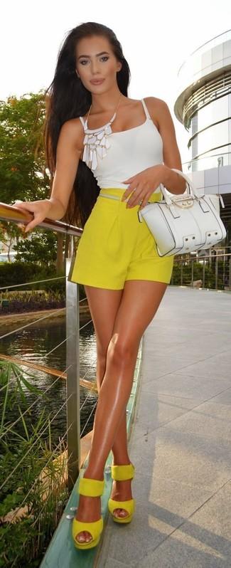 Cómo combinar: bolso de hombre de cuero blanco, sandalias de tacón de ante amarillas, pantalones cortos amarillos, camiseta sin manga blanca