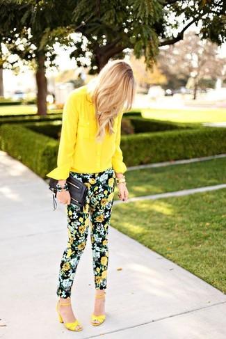 Cómo combinar: cartera sobre de cuero negra, sandalias de tacón de cuero amarillas, pantalones pitillo con print de flores negros, camisa de vestir de gasa amarilla