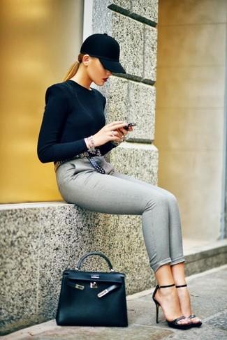 Cómo combinar: bolso de hombre de cuero negro, sandalias de tacón de cuero negras, pantalones pitillo grises, jersey con cuello circular negro