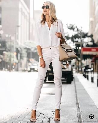 Cómo combinar: bolsa tote de cuero marrón claro, sandalias de tacón de cuero en beige, vaqueros pitillo desgastados blancos, blusa de botones de seda blanca