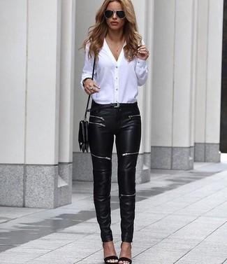 Cómo combinar: bolso bandolera de cuero negro, sandalias de tacón de cuero negras, vaqueros pitillo de cuero negros, blusa de botones blanca