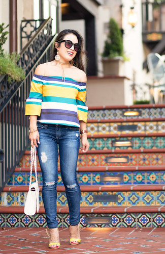 Cómo combinar: bolso bandolera de cuero blanco, sandalias de tacón de cuero amarillas, vaqueros pitillo desgastados azules, top con hombros descubiertos de rayas horizontales en multicolor
