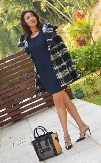 Cómo combinar: zapatos de tacón de cuero con tachuelas negros, sandalias de tacón de cuero con tachuelas en blanco y negro, vestido recto azul marino, abrigo de tartán en negro y blanco