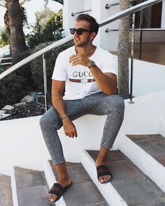 Outfits hombres en clima caliente: Intenta ponerse una camiseta con cuello circular estampada blanca y un pantalón chino de tartán gris transmitirán una vibra libre y relajada. Si no quieres vestir totalmente formal, opta por un par de sandalias de cuero de rayas horizontales negras.