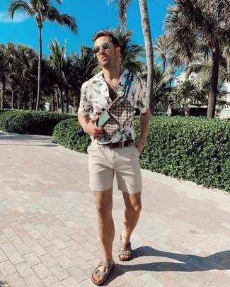 Look de moda: Riñonera de lona estampada marrón, Sandalias de cuero grises, Pantalones cortos en beige, Camisa de manga corta con print de flores blanca