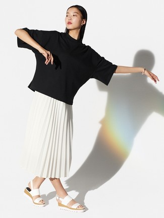 Cómo combinar: sandalias planas de cuero blancas, falda midi plisada blanca, camiseta con cuello circular negra