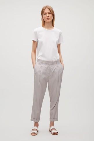 Cómo combinar: sandalias planas de cuero blancas, pantalón chino gris, camiseta con cuello circular blanca