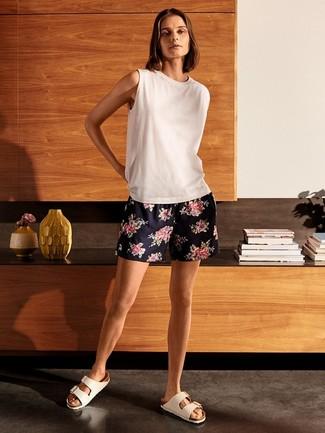 Cómo combinar: sandalias planas de cuero blancas, pantalones cortos con print de flores azul marino, camiseta sin manga blanca