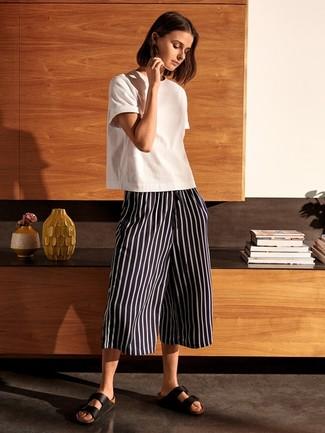 Cómo combinar: sandalias planas de cuero negras, falda pantalón de rayas verticales en negro y blanco, camiseta con cuello circular blanca