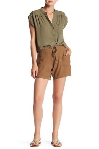 Cómo combinar: sandalias planas de cuero plateadas, pantalones cortos de leopardo marrónes, blusa sin mangas verde oliva
