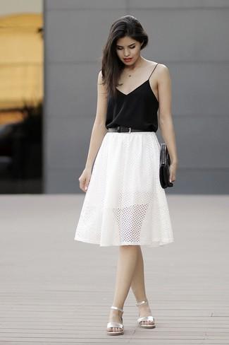 Cómo combinar: cartera sobre de cuero negra, sandalias planas de cuero plateadas, falda skater con ojete blanca, camiseta sin manga de seda negra