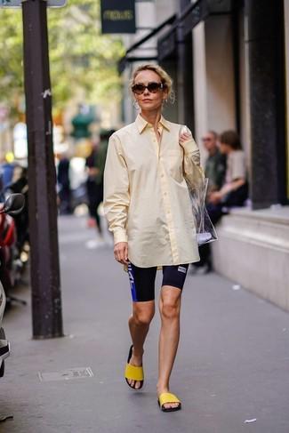 Look de moda: Bolsa tote de goma transparente, Sandalias planas de goma amarillas, Mallas ciclistas estampadas negras, Camisa de vestir amarilla