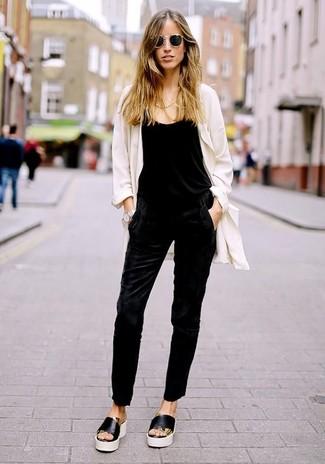 Cómo combinar: gafas de sol negras, sandalias planas de cuero en negro y blanco, mono negro, abrigo duster blanco