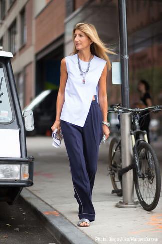 Cómo combinar: collar plateado, sandalias planas de cuero plateadas, pantalones anchos azul marino, blusa sin mangas celeste