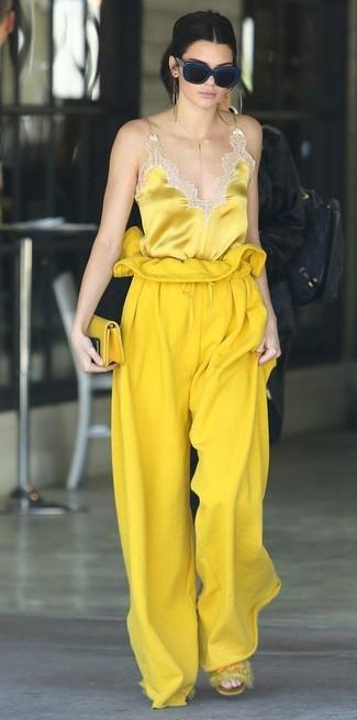 Cómo combinar: cartera sobre de cuero amarilla, sandalias planas de pelo amarillas, pantalones anchos amarillos, camiseta sin manga de seda amarilla