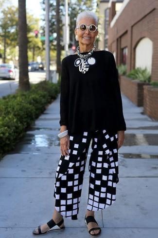 Combinar un jersey oversized negro para mujeres de 60 años: Ponte un jersey oversized negro y unos pantalones anchos a cuadros en negro y blanco y te verás como todo un bombón. ¿Te sientes valiente? Completa tu atuendo con sandalias planas de cuero negras.